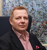 Kehittämispäällllikö Jukka Lindberg värikkään taulun edessä.