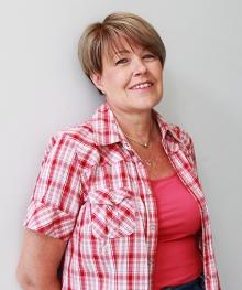 Kirjoittaja Marianne Pentikäinen katsoo iloisesti hymyillen kameraan päällään kirkkaan vaaleanpunainen pusero.