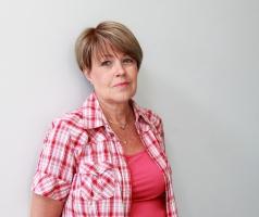 Kirjoittaja Marianne Pentikäinen nojaa takana olevaan valkoiseen seinään ja katsoo vakaasti kohti kameraa.