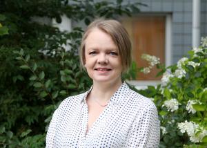Annemaria Ojanperä kukkivien pensaiden luona.