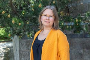 Anne Kallio mäntujen edessä keltaisess villatakissa.