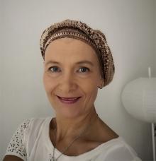 Kirjoittaja Jaana Pakarinen hymyilee iloisesti läheltä otetussa kasvokuvassa.