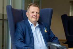 Jukka Lindberg sinisessä tuolissa sininen takki päällä.
