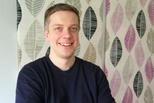 Joni Ulmanen tekstiilitaulun edessä, taulussa harmaita, mustia, ruskeita ja liloja lehtikuvioita.