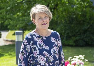 Marianne Pentikäinen kukallisessa puserossa, kuvassa puita ja kesäkukkia.