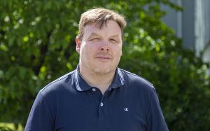 Pasi Ylipaavalniemi sininen paita päällä pihalla puiden edessä.