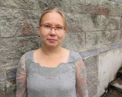 Kirjoittaja Anne Kallio seisoo harmaan kiviseinän edessä.