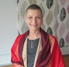 Kirjoittaja Jaana Pakarinen hymyilee kohti kameraa punainen neule hartioillaan.