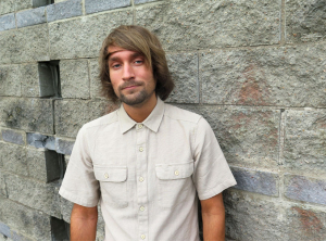 Lasse Westerinen standing in front of the grey stone wall.