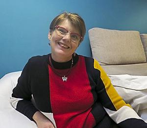 Tiina Jäppinen istuu turkoosin seinän edessä valkoisessa säkkituolissa.