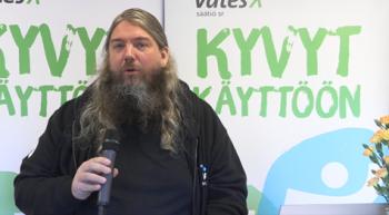 Kimmo Kumlander mikrofoni kädessä, pitkät hiukset ja parta.