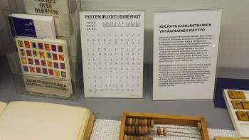 Kuva Näkövammaismuseosta. Kuvassa on pistekirjoitusmerkkejä ja vanha helmilaskukone.