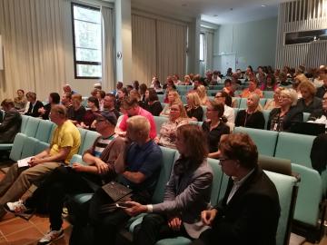 Auditorio on lähes täynnä osallistujia.